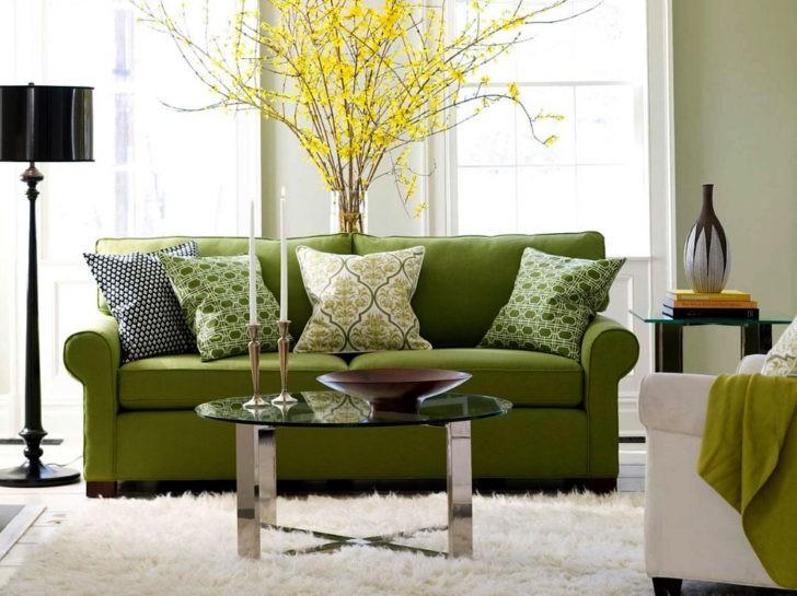 Salón con sofá verde junto a la ventana